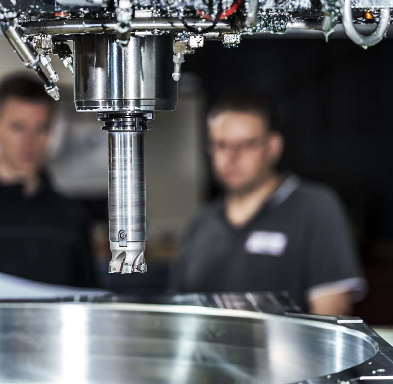 Industriefoto CNC Fräskopf mit Werkstück und Personen im Hintergrund