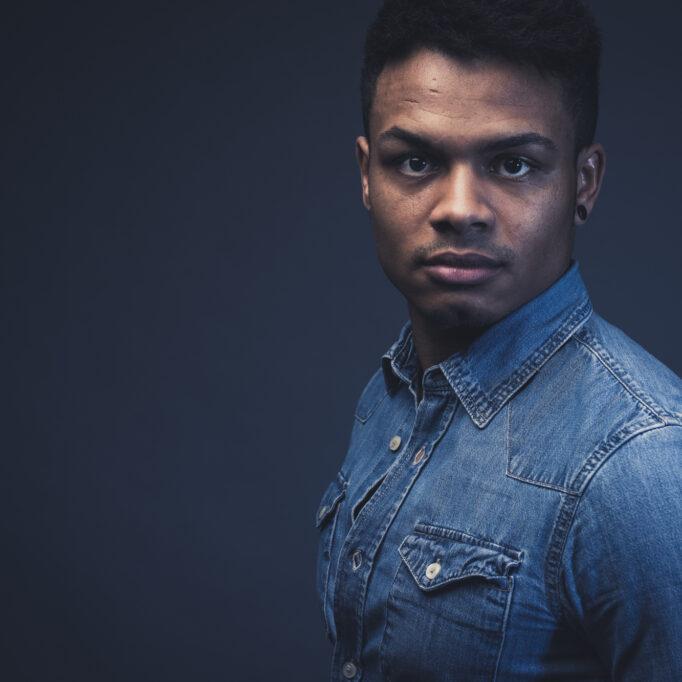 Modefotografie im Studio junger Mann mit JeansHemd männlich dunkle Stimmung