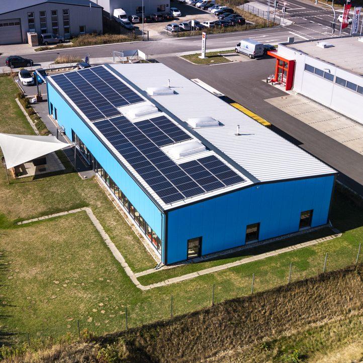 Drohnen Luftaufnahmen einer blauen Industriehalle mit Sonnensegel und Photovoltaik-Anlage