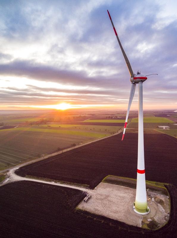 Drohnen Luftaufnahme einer Windkraftanlage kurz vor Fertigstellung im Gegenlicht mit Sonnenaufgang